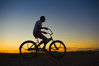 Silhouette of Hispanic man riding bicycle at sunset