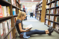 Hispanic woman reading book on floor in bookstore