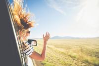 Hispanic woman leaning head out car window 11018072288| 写真素材・ストックフォト・画像・イラスト素材|アマナイメージズ