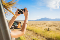 Hispanic woman photographing landscape out car window