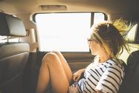 Hispanic woman looking out car window 11018072293| 写真素材・ストックフォト・画像・イラスト素材|アマナイメージズ