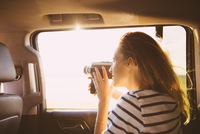 Hispanic woman recording out car window