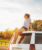 Hispanic woman relaxing on car roof