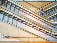 High angle view of Hispanic man riding escalator