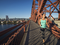 Caucasian woman jogging on urban bridge, Portland, Oregon, United States