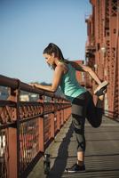 Caucasian woman stretching on urban bridge