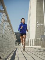 Caucasian woman jogging on urban bridge