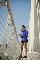 Caucasian woman using cell phone on urban bridge