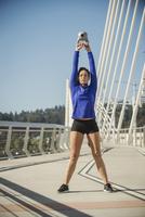 Caucasian woman working out on urban bridge