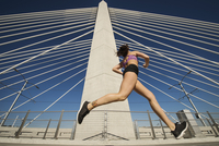 Low angle view of Caucasian woman jogging on urban bridge