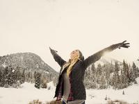 Caucasian woman playing in snow 11018072347| 写真素材・ストックフォト・画像・イラスト素材|アマナイメージズ
