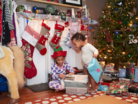 Mixed race children opening Christmas gifts