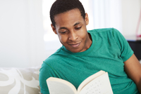 African American man reading book on bed