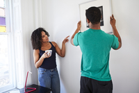 Couple hanging picture in new apartment