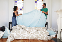 Couple changing sheets on bed