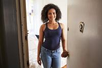 Mixed race woman opening apartment door