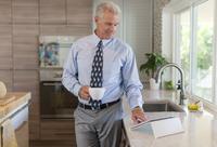 Caucasian businessman using digital tablet in kitchen