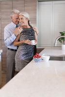 Caucasian couple hugging in kitchen 11018072420| 写真素材・ストックフォト・画像・イラスト素材|アマナイメージズ