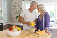 Caucasian couple touching foreheads in kitchen 11018072421| 写真素材・ストックフォト・画像・イラスト素材|アマナイメージズ