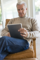 Caucasian man using digital tablet in armchair