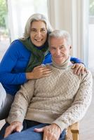 Caucasian couple hugging in armchair 11018072426| 写真素材・ストックフォト・画像・イラスト素材|アマナイメージズ