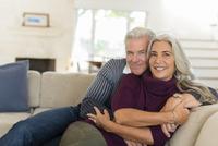 Caucasian couple hugging on sofa 11018072430| 写真素材・ストックフォト・画像・イラスト素材|アマナイメージズ