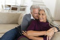 Caucasian couple hugging on sofa 11018072431| 写真素材・ストックフォト・画像・イラスト素材|アマナイメージズ