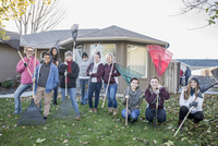 Smiling friends posing with rakes on autumn lawn