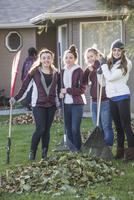 Smiling girls raking autumn leaves