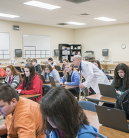 Teacher helping students use laptops in science classroom