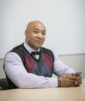 Black businessman using cell phone in office