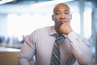 Black businessman resting hand on chin in office