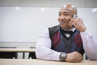 Black businessman talking on cell phone in office
