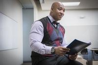 Black businessman reading folder in conference room