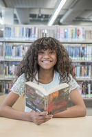 Smiling girl reading book in library