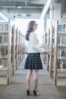 Student carrying stack of books in library 11018072585| 写真素材・ストックフォト・画像・イラスト素材|アマナイメージズ