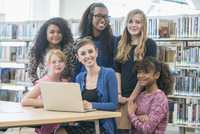 Mentor helping students use laptop in library