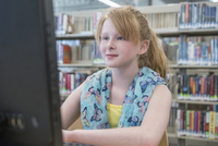 Caucasian student using computer in library