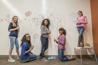 Girls drawing on whiteboard