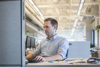 Caucasian businessman working in office cubicle 11018072654| 写真素材・ストックフォト・画像・イラスト素材|アマナイメージズ