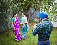 Man photographing women in traditional Indian dresses