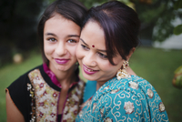 Mother and daughter in Indian clothing hugging outdoors