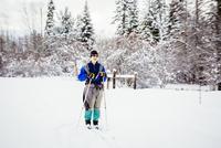 Caucasian woman cross-country skiing in snowy field