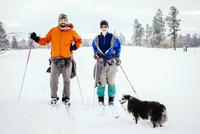 Caucasian couple and dog cross-country skiing in snowy field 11018072739| 写真素材・ストックフォト・画像・イラスト素材|アマナイメージズ