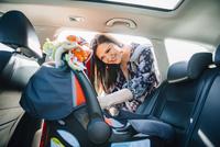 Hispanic mother fastening car seat in car 11018072753| 写真素材・ストックフォト・画像・イラスト素材|アマナイメージズ