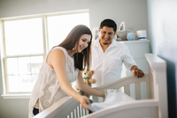Hispanic couple preparing crib bed in nursery
