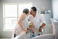 Hispanic couple kissing in nursery