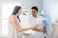 Hispanic couple setting up nursery furniture