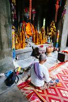Woman sitting near Buddhist shrine