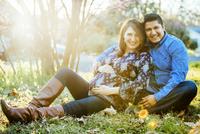 Pregnant Hispanic couple smiling outdoors